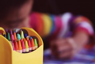Un enfant en train de dessiner avec des feutres