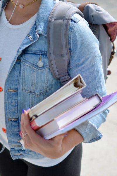 Une adolescente en tenue civile avec des cahiers en main.